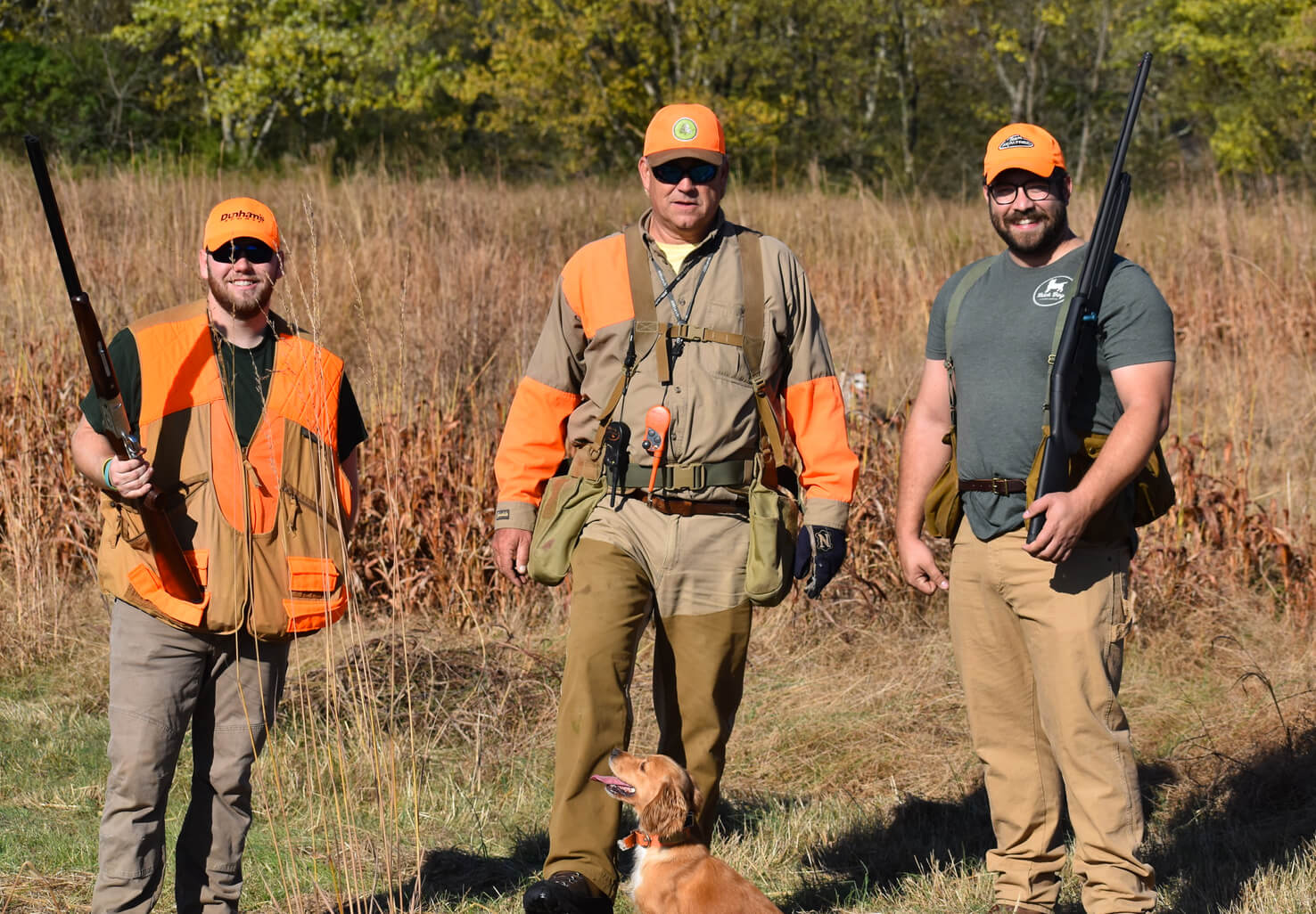 happy group of hunters with dog